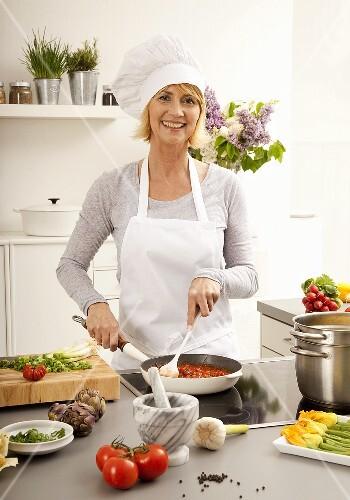 Hobbyköchin beim Tomatensauce kochen