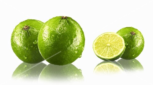 Limes, whole and halved, with drops of water and reflections