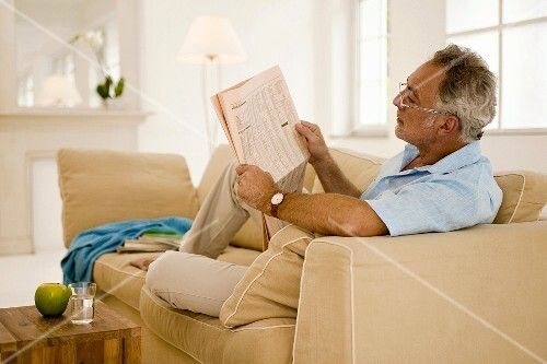 Mature man reading newspaper on sofa, side view