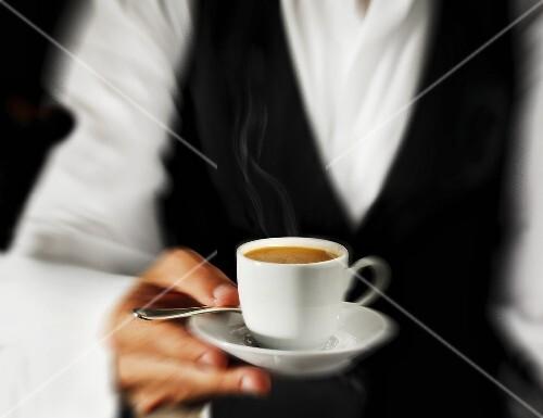 Waiter serving espresso