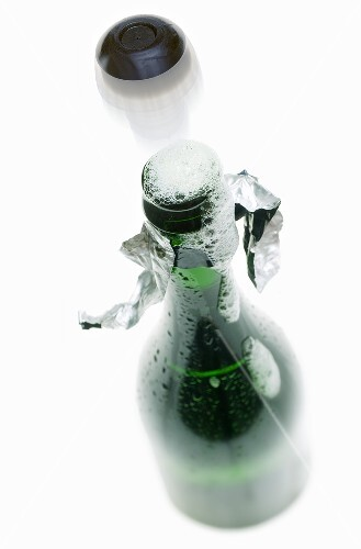 Cork flying out of bottle of sparkling wine