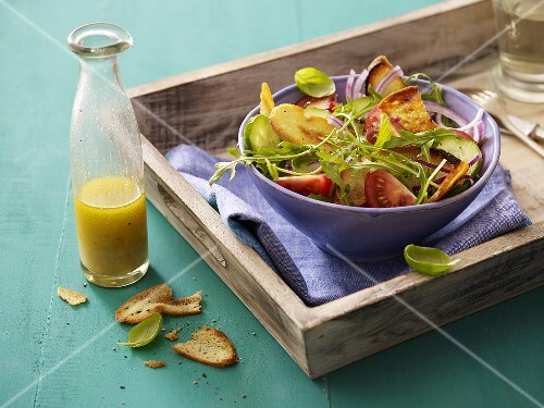 Bread salad with tomatoes and rocket, salad dressing in bottle