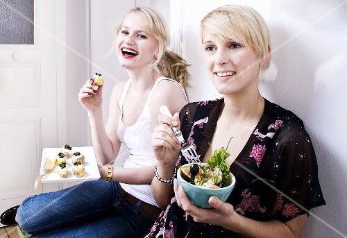 Two women eating appetisers