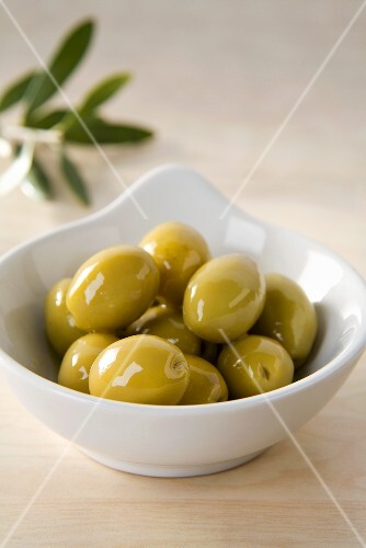 Green olives in small dish in front of olive sprig
