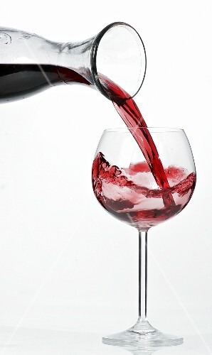 Pouring red wine into glass from carafe