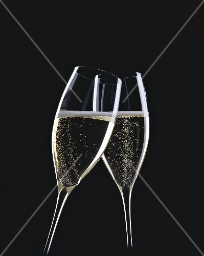 Two glasses of sparkling wine being clinked together