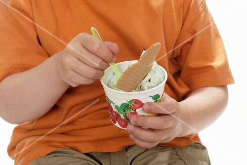 Boy eating peppermint ice cream from a small tub
