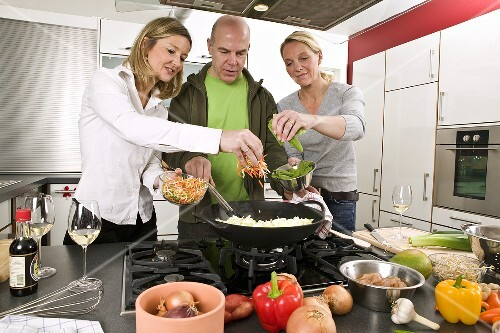 Man and two women cooking a stir-fry together