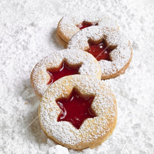 Four Linzer biscuits on icing sugar