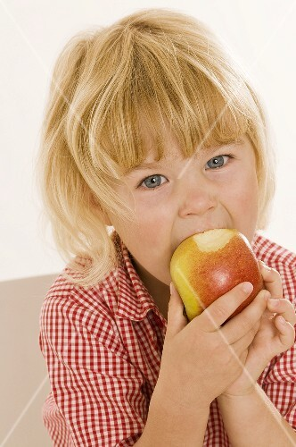 Little girl eating an organic apple