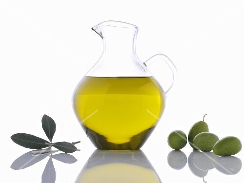 Olive oil in carafe, green olives and olive leaves