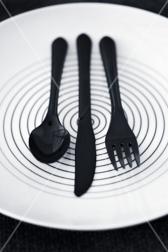 Black plastic cutlery on a plate
