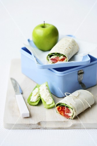 A lunchbox with wraps and an apple