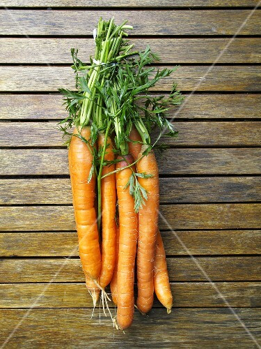Fresh carrots on a wooden surface, seen from above