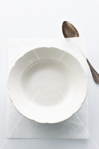 An empty plate on a piece of paper with a spoon next to it