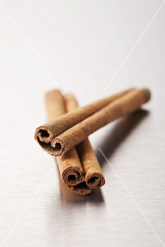 Two cinnamon sticks on a metal surface