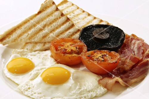 English breakfast with fried egg, bacon, tomatoes, mushrooms and toast