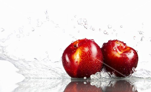 Two plums being washed