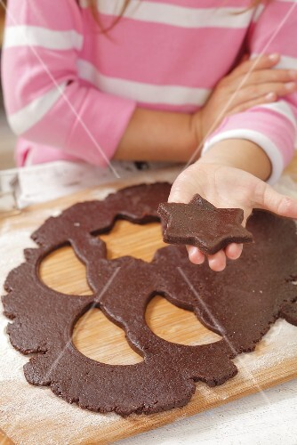 A girl holding a cut-out star-shaped biscuit
