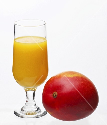 A glass of mango juice with a mango beside it