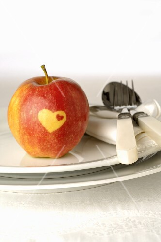 Red apple with heart on plate with cutlery