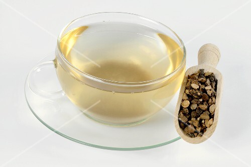 Cup of tea with dried nutgrass root in a scoop