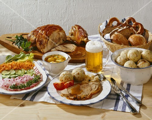 Soup, salad and roast pork with dumplings and beer