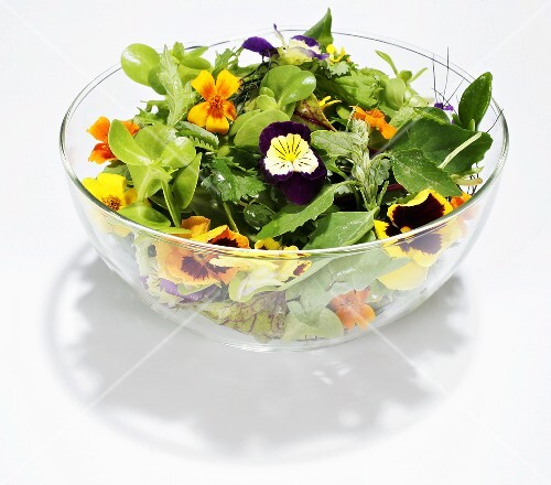 Salad leaves with flowers in glass bowl