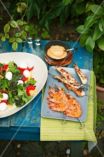Mango salad with mini mozzarella, chicken satay, prawn skewers and a dip on a table outside