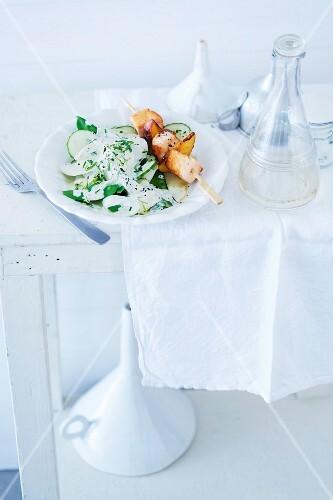 Vegetable salad with cucumber, kohlrabi, radish and salmon kebabs