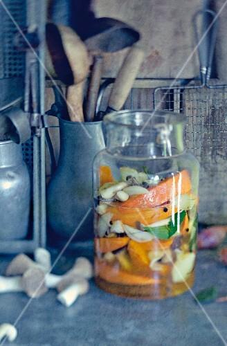 Pumpkins and mushrooms in a vinegar broth in a preserving jar
