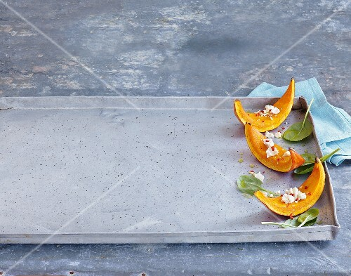 Roasted pumpkin wedges on a baking tray