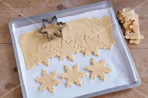 Snowflake shapes being cut out of biscuit dough