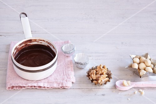 An arrangement of nuts, praline tins and liquid chocolate