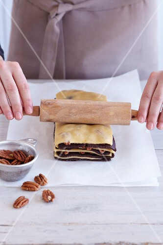 Zebra biscuits being made: light and dark pastry being layered with pecan nuts