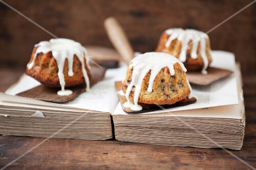 Mini eggnog Bundt cakes with icing sugar on a book