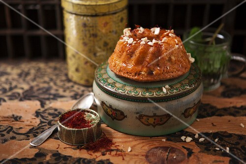 A mini Oriental Bundt cake with cashew nuts and a tin of saffron threads