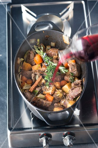 Venison ragout being made: red wine being poured over vegetables and meat
