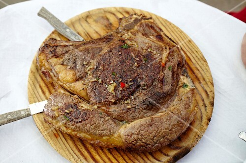 A pork chop on a wooden board