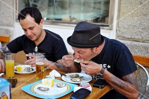 Two men eating fresh oysters (Galicia, Spain)