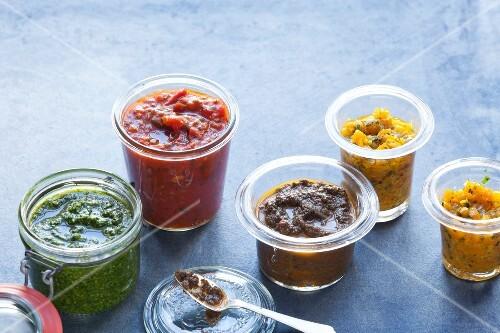 Various sauces and pestos in jars