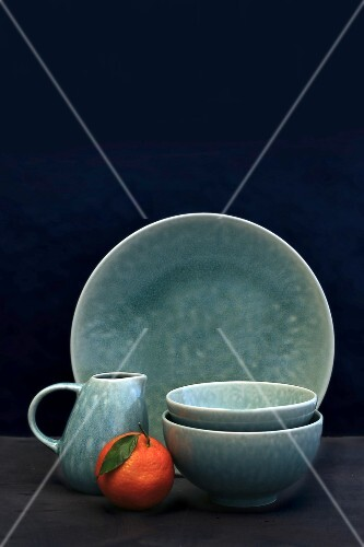 Plate, and milk jug and bowls against a black background
