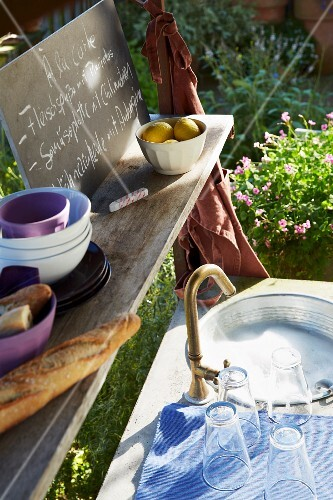 Glasses and crockery in a sink in a garden