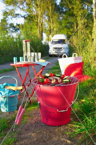 A barbecue, a camping table and a basket on the edge of a road