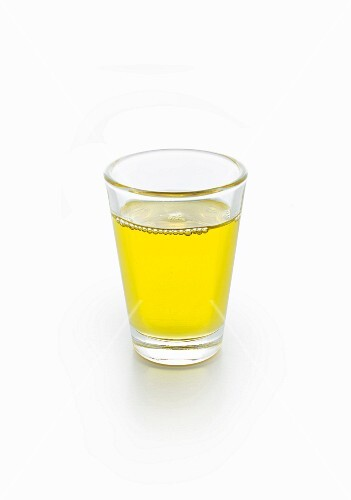 A glass of moringa oil on a white surface