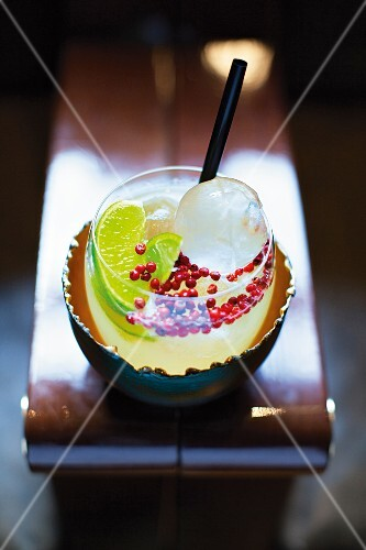 A Caipirinha with pink peppercorns and round ice cubes