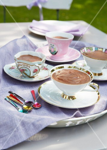 Chocolate mousse in various cups with saucers