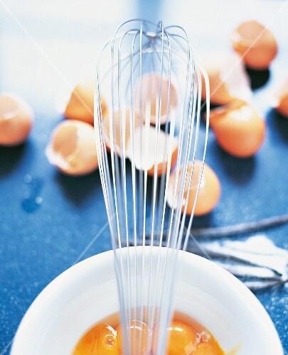 A whisk balanced over a bowl of beaten eggs