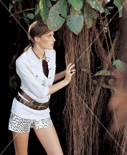 Frau in weißer Bluse + Leoprint Short, Gürtel hinter einem Baum