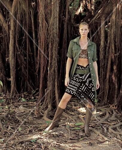 Frau in Hemdblusenkleid + Rock, Ledergürtel, Stiefel, im Dschungel
